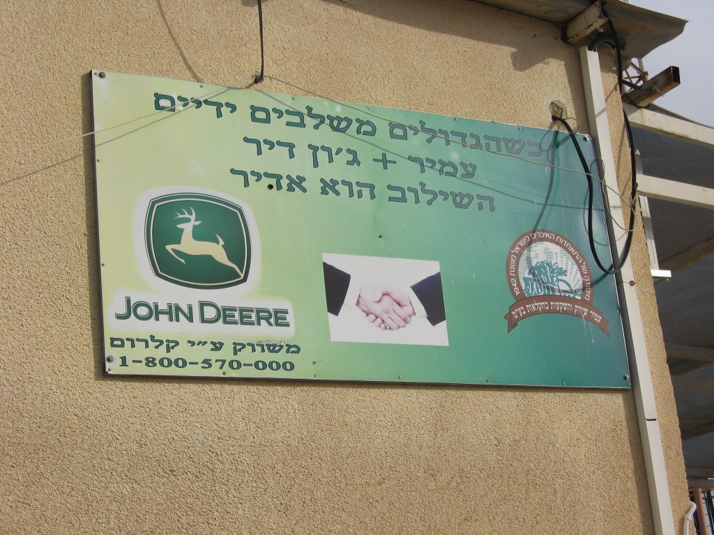 Signage on a packing house in the illegal settlement of Na'ama on the occupied Jordan Valley: 'When the great join hands -Amir + John Deere'. Photo: Corporate Watch, January 2013