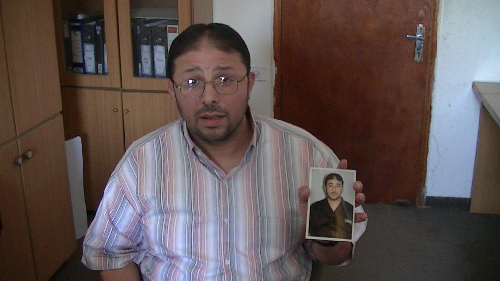 Akram Salameh holds up a picture of himself in prison uniform, taken inside Ramleh prison hospital
