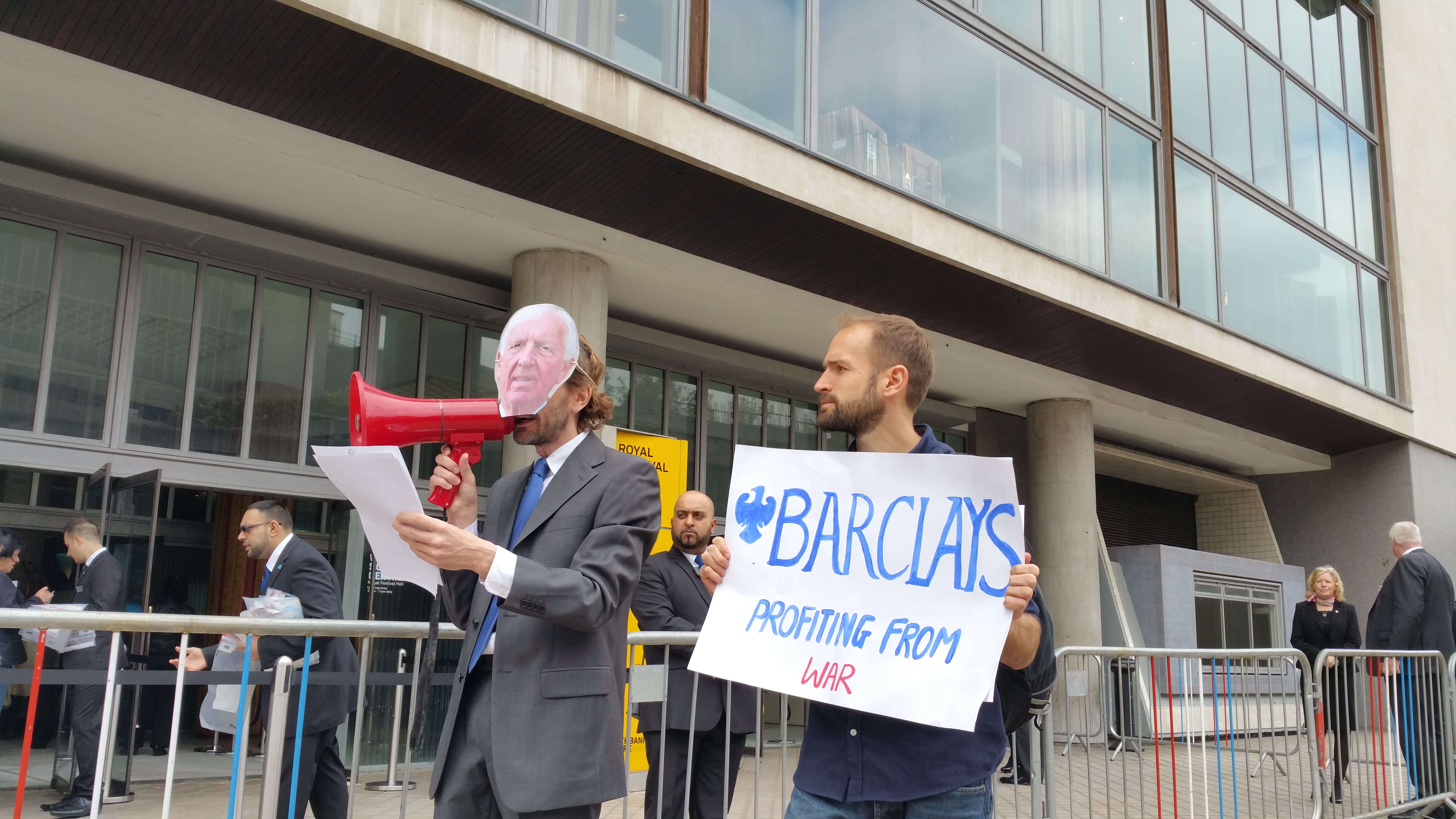 An activist reads out an alternative chairman's speech outside the Barclays AGM